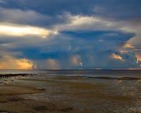 在看暴风云的海滩的日落 库存图片