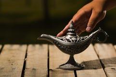 在真实的Aladin样式,轻轻地接触它的手的美丽的古色古香的金属灯,坐木表面 免版税库存照片