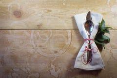 在真正土气木桌上的简单的国家圣诞节餐位餐具与霍莉离开 免版税图库摄影