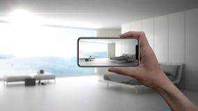 在真正的家,建筑师设计师概念递拿着巧妙的电话, AR应用,模仿家具和室内设计产品 免版税库存图片