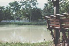 在眺望台的木长凳在池塘海滨在公园 库存照片