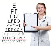 在眼力测试图附近的女性医生 库存图片