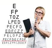 在眼力测试图附近的女性医生 免版税库存照片