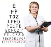 在眼力测试图附近的女性医生 图库摄影