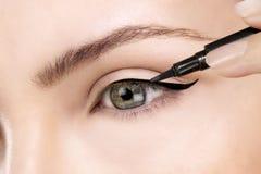在眼睛的美丽的式样申请的眼线膏特写镜头 免版税库存图片