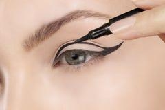 在眼睛的美丽的式样申请的眼线膏特写镜头 库存图片