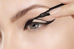 在眼睛的美丽的式样申请的眼线膏特写镜头 免版税库存照片