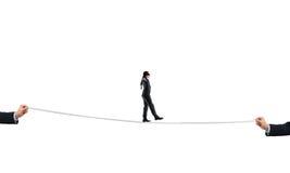在眼罩的年轻商人反对白色背景走在绳索的 免版税图库摄影