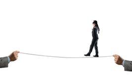 在眼罩的年轻商人反对白色背景走在绳索的 免版税库存图片