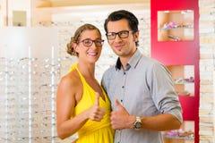 在眼镜师的年轻夫妇戴眼镜 图库摄影
