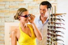 在眼镜师的年轻夫妇戴眼镜 免版税库存图片