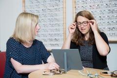 在眼镜师选择新的玻璃的商店妇女 免版税库存图片