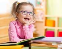 在眼镜阅读书的聪明的孩子在她的屋子里 免版税库存图片