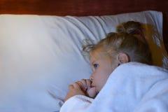在睡眠期间,孩子在床上吮一个手指在上床时间前和 免版税库存图片