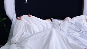 在睡衣打扮的三个女孩用毯子盖并且上床 纵容在床上的乐趣 股票录像