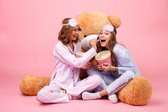 在睡衣打扮的两个快乐的俏丽的女孩 免版税图库摄影