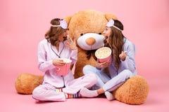在睡衣打扮的两个愉快的俏丽的女孩 免版税库存照片