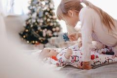 在睡衣打扮的女孩看她说谎在床上的微小的兄弟在有新年的树的舒适屋子 免版税库存照片