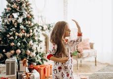 在睡衣打扮的迷人的女孩拿着在有很多的一朵花有新年的树的轻的舒适室 库存图片