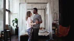 在睡衣的不同种族的夫妇跳舞 非洲愉快男性和白种人女性的看起来,笑和微笑,握手 免版税库存图片