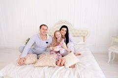 在睡衣的微笑和看camer的愉快的家庭画象  库存照片