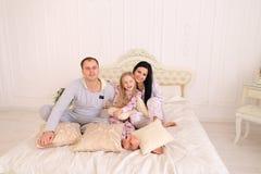 在睡衣的微笑和看camer的愉快的家庭画象  库存图片