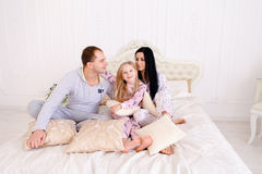 在睡衣的微笑和看camer的愉快的家庭画象  图库摄影