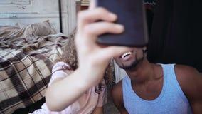 在睡衣的愉快的多种族夫妇拍在智能手机的selfie照片 男人和妇女微笑和亲吻,无忧无虑的早晨 影视素材
