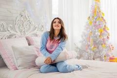 在睡衣的模型临近圣诞树 免版税库存照片