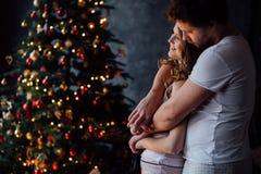 在睡衣的美好的年轻夫妇在恰好装饰的圣诞树背景 免版税库存照片