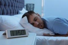 在睡觉在床上的桌和年轻人上的闹钟 免版税库存图片