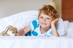 在睡觉的可爱的孩子男孩在他的与玩具的白色床上以后 库存图片