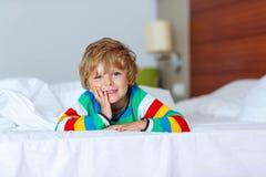 在睡觉的可爱的孩子男孩在他的与玩具的白色床上以后 免版税库存图片