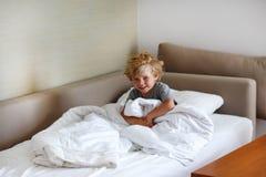 在睡觉的可爱的孩子男孩在他的白色床上以后 免版税库存照片