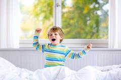 在睡觉的可爱的愉快的小孩男孩在他的在五颜六色的睡衣的白色床上以后 库存照片