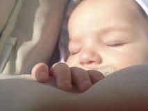 在睡觉的四个月的男婴的手 库存图片