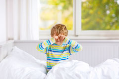 在睡觉的愉快的小孩男孩在五颜六色的睡衣的床上以后 库存图片
