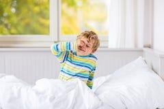 在睡觉的愉快的小孩男孩在五颜六色的睡衣的床上以后 免版税库存图片