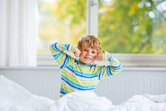 在睡觉的愉快的小孩男孩在五颜六色的睡衣的床上以后 图库摄影