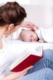 在睡觉的婴孩旁边的母亲读书 免版税库存照片
