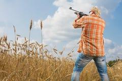 在瞄准枪的盖帽和太阳镜的猎人领域 库存图片