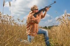 在瞄准枪的盖帽和太阳镜的猎人领域 免版税库存照片