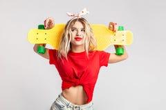 在短的牛仔布短裤和一件红色T恤杉打扮的少女摆在与一个黄色滑板在演播室 库存图片