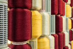 在短管轴的红色和黄色丝绸线程数 库存图片