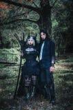 在矮子幻想市场期间,恶魔般夫妇在森林里摆在 免版税库存照片
