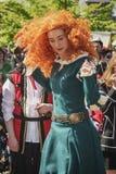 在矮子爱好者期间,有红色假发的美丽的少妇跳舞 免版税库存图片
