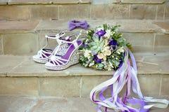 在石台阶的紫色婚姻的辅助部件花束蝶形领结 库存照片