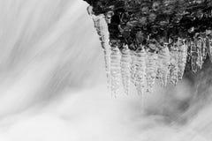 在石和流动的水的冰柱下 库存图片