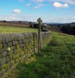 在石块墙旁边打开有方向标的乡下 免版税库存图片