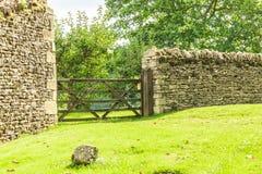 在石块墙的土气门在Bibury英国英国 图库摄影